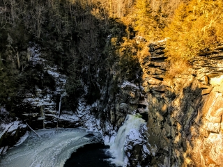 frozen pool with waterfall pouring in from above mountain cliff