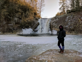 a woman stands on a rock next to a partially frozen pool with icy water pouring in from a nearby waterfall