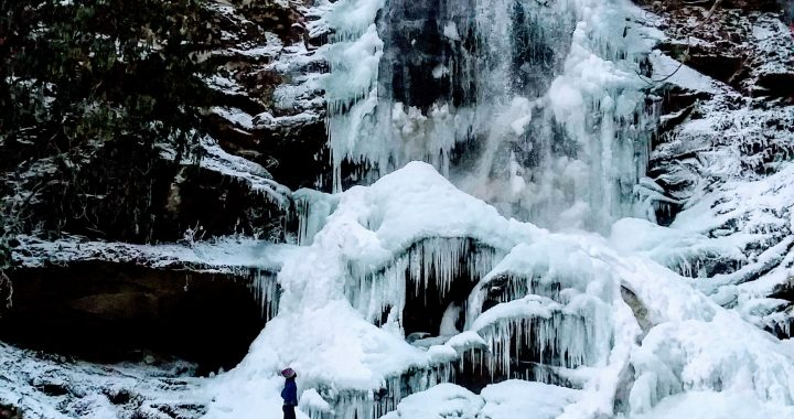large frozen waterfall in the woods with woman standing in front looking up