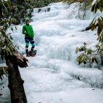 frozen meandering waterfall with woman in green jacket and hat standing on ice