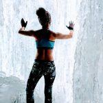 woman in ice cave touching frozen wall wearing workout clothes