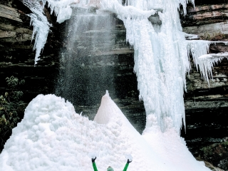 woman holding blocks of ice at bottom of a freezing waterfall