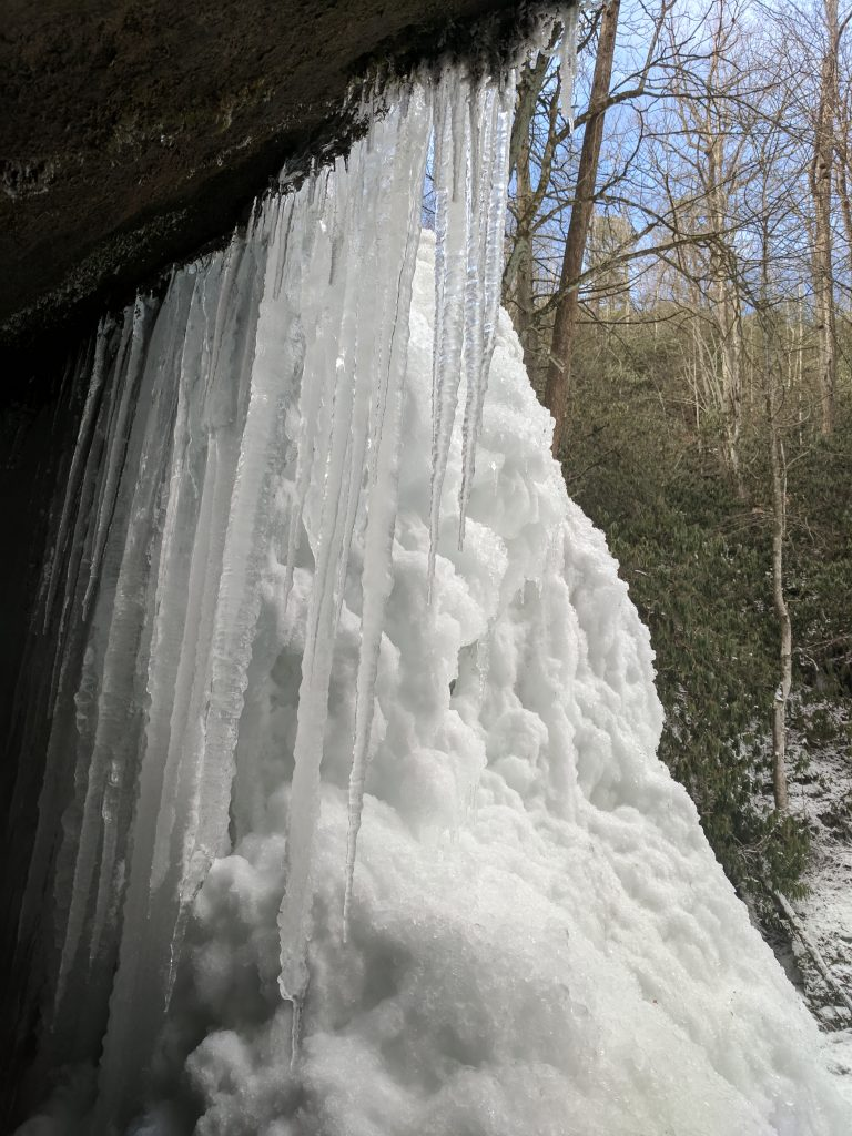 icicles and a snowdrift form on the face of an overhanging rock near the Blue Ridge Parkway